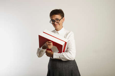 Skeptical looking conservatively clothed female teacher holding heavy bright binders against white background