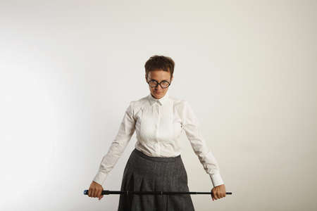 Strict looking conservatively dressed female teacher with a long black pointer against white wall background
