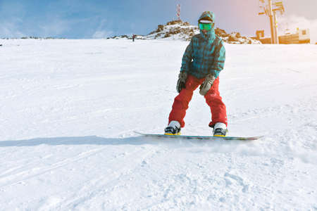 Beginner snowboarder girl wears her google mask and bright clothes, practice her riding skills with backside edge breaking on top of snowy ski slope near lift, isolated on right side