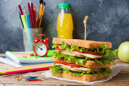 Photo for Healthy lunch for school with sandwich, fresh apple and orange juice. Assorted colorful school supplies. Copy space - Royalty Free Image