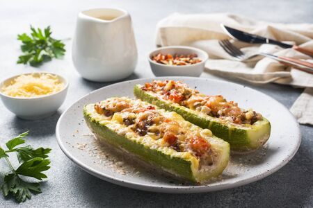 Photo pour Baked stuffed zucchini boats with minced chicken mushrooms and vegetables with cheese on a plate - image libre de droit