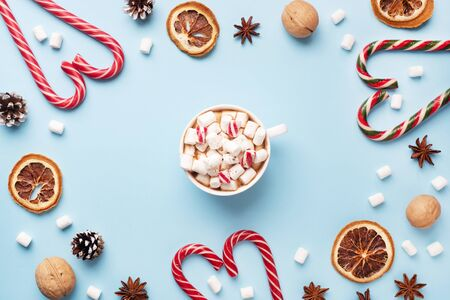 Photo pour Cup of hot chocolate with marshmallow cocoa powder and caramel nuts, oranges on pastel blue background with copy space. Christmas winter concept - image libre de droit