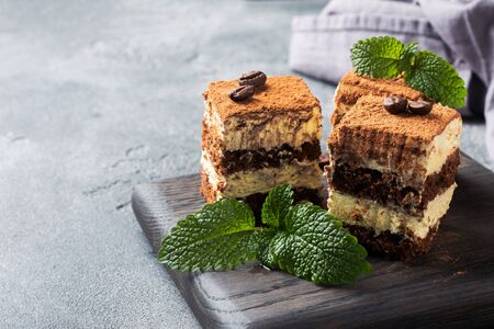 Photo pour Pieces of tiramisu cake with delicate cream, coffee beans and mint leaves Dark concrete background with copy space. - image libre de droit