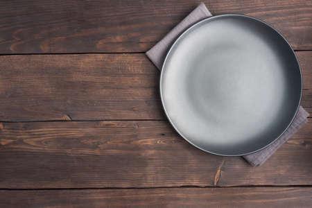 Photo pour Empty black plate on wooden rustic background. Top view with copy space - image libre de droit