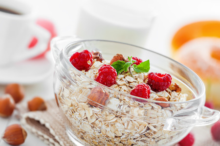 Delicious healthy food breakfast. Oatmeal  muesli with raspberry and hazelnut on table.