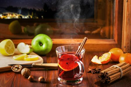 Mulled wine with citrus fruits and cinnamon on a table. Traditional winter hot drink for Christmas Eve party by window. Starry night winter landscape on background.