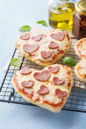 Foto de Baked heart shaped homemade pepperoni mini pizza. Happy Valentines day. Romantic dinner concept. - Imagen libre de derechos