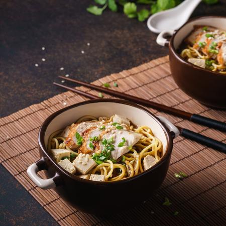Foto de Japanese ramen bowl with chicken and tofu. Dark background. - Imagen libre de derechos