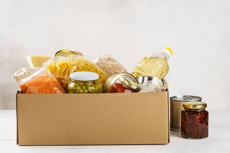 Photo pour Various canned food, pasta and cereals in a cardboard box. Food donations or food delivery concept. - image libre de droit