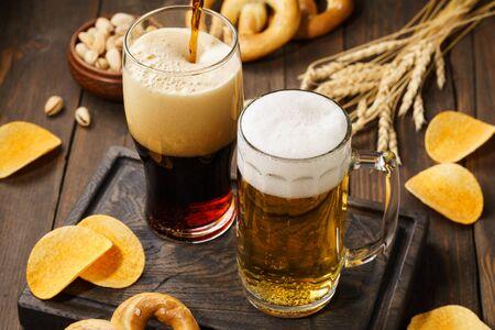 Foto de Light and dark beer with various snacks - chips, pretzels and nuts on a dark wooden background. - Imagen libre de derechos