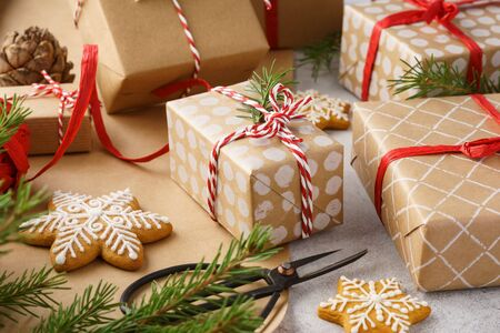 Photo for Handcrafted Christmas gift boxes, wrapping paper, cookies, red ribbon and twine. Winter holidays preparation. Xmas mood. - Royalty Free Image