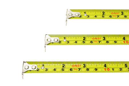 Measuring tapes of different lengths extended horizontally on white background with copy space
