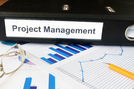 Graphs and file folder with label  Project Management.