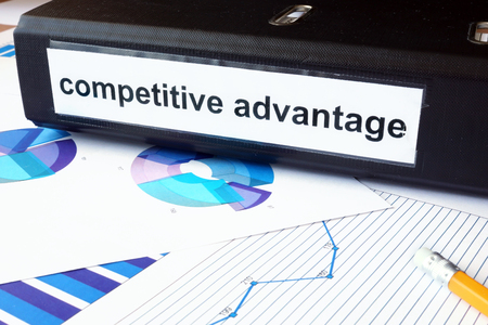Graphs and file folder with label competitive advantage.