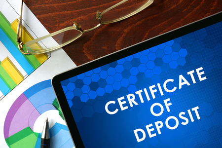 Photo pour Tablet with certificate of deposit CD on a table. Business concept. - image libre de droit