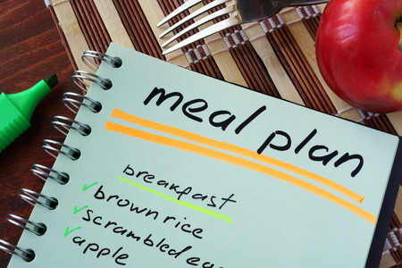 Photo pour Notepad with meal plan and apple. Diet planning. - image libre de droit
