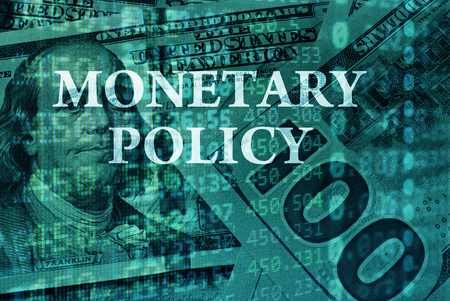 Words Monetary policy  with the financial data on the background.