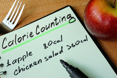 Photo pour Diary with a record Calorie counting on a table. - image libre de droit