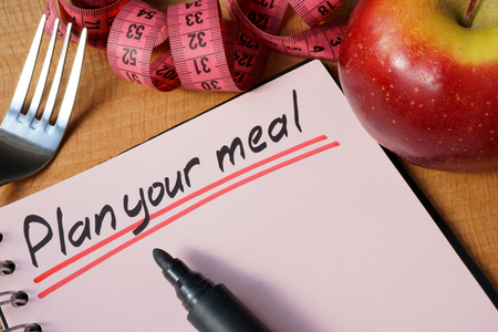 Photo for Diary with a record plan your meal on a table. - Royalty Free Image
