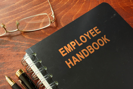 Foto de Employee handbook on a wooden table and glasses. - Imagen libre de derechos