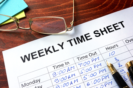 Foto de Paper with weekly time sheet on a table. - Imagen libre de derechos