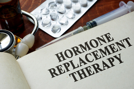 Book with words hormone replacement therapy on a table.