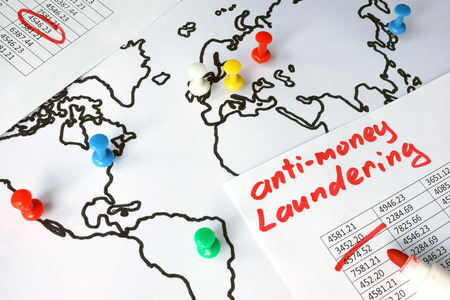 Photo pour Anti-money laundering (AML) concept. Data and thumb tacks in a map. - image libre de droit