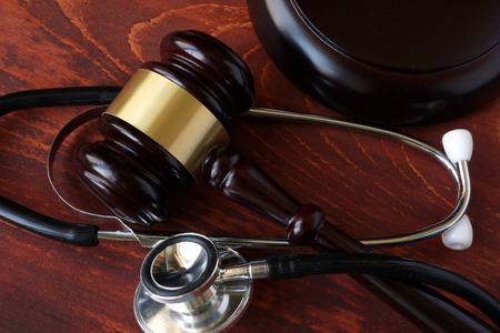 Photo for Gavel and stethoscope on a wooden surface. - Royalty Free Image