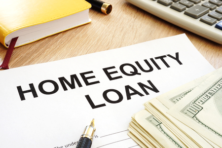 Home equity loan form and cash on a table.