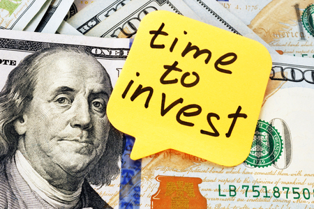 Time to invest concept. Memo stick and money.