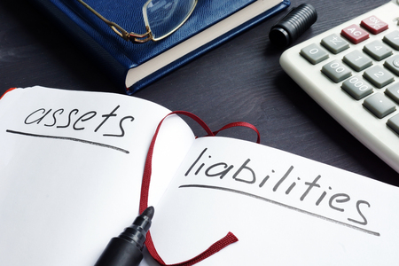 List of assets vs liabilities in the note pad.