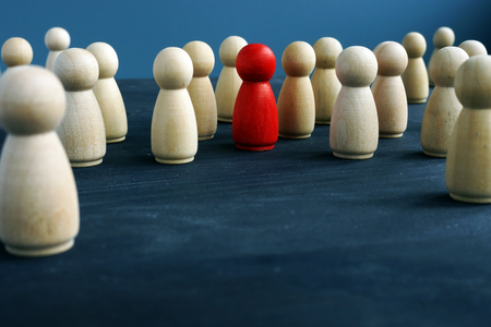 Foto de Wooden figures and one red figure. Be different. Stand out from the crowd. - Imagen libre de derechos