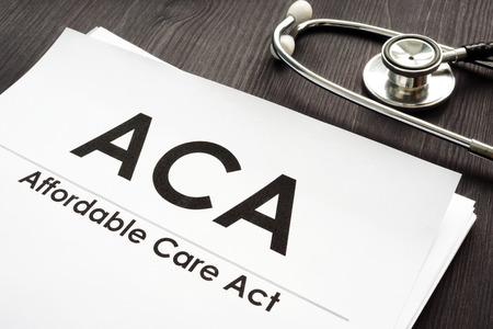 Affordable Care Act ACA and stethoscope on a wooden desk.
