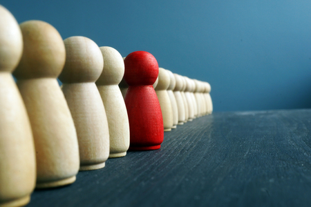 Photo pour Leadership development. Line of wooden figurines with red one. - image libre de droit