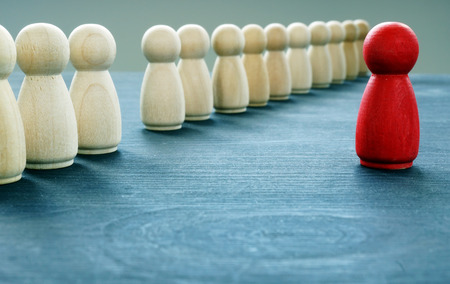 Foto de Be unique and different. Red figurine is stand out from the crowd. - Imagen libre de derechos