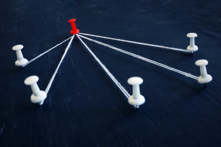White push pins and red one connected by thread. Leadership, management and delegating.