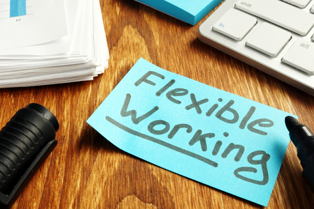 Foto de Flexible working policy concept. Piece of paper on table. - Imagen libre de derechos