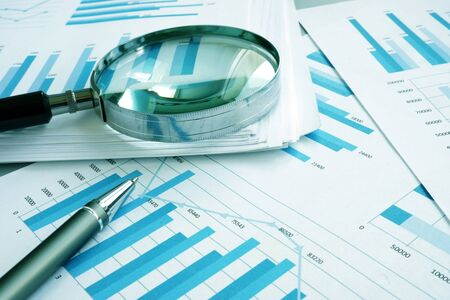 Foto de Assessment and audit. Business papers with financial charts and Magnifying glass. - Imagen libre de derechos
