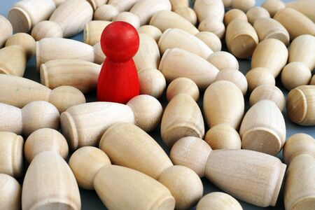 Successful leader in the business. Red wooden figurine. Competitive edge.