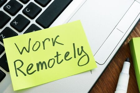 Photo for Work Remotely memo stick. Laptop for remote job. - Royalty Free Image