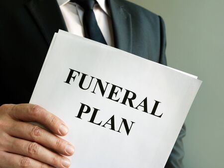 Photo pour Man holds Funeral plan and stack of papers. - image libre de droit