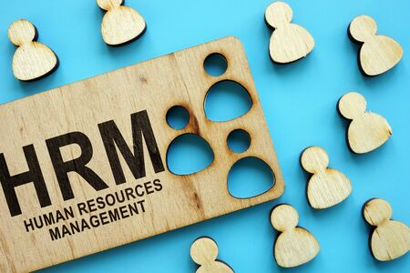 HRM human resources management concept. Wooden figures on the blue background.