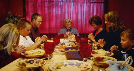 Family praying around Thanksgiving table