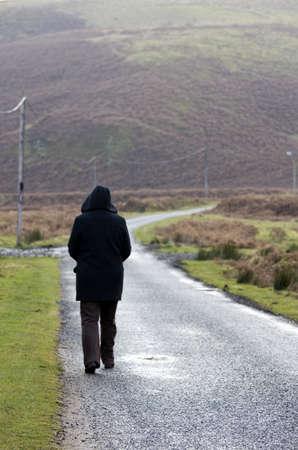 Person walking down rural road,  Northumberland, England
