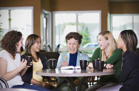 Group of girls listening to senior woman in restaurant