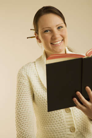 A woman smiling and reading book
