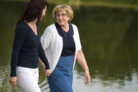 Two women walking beside a lake