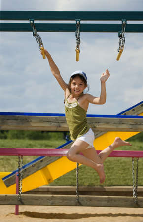 Girl swinging on monkey bars