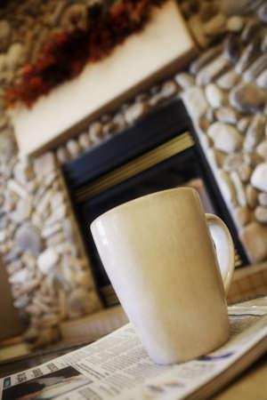Coffee mug on table with newspaper