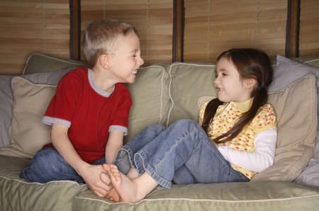Boy and girl playing on a couch
